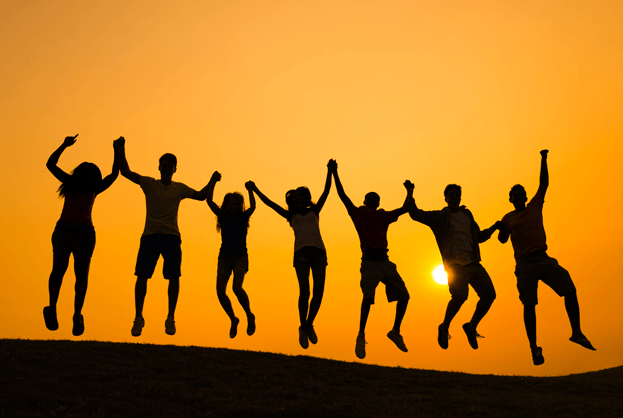 people jumping on a hill at sunrise