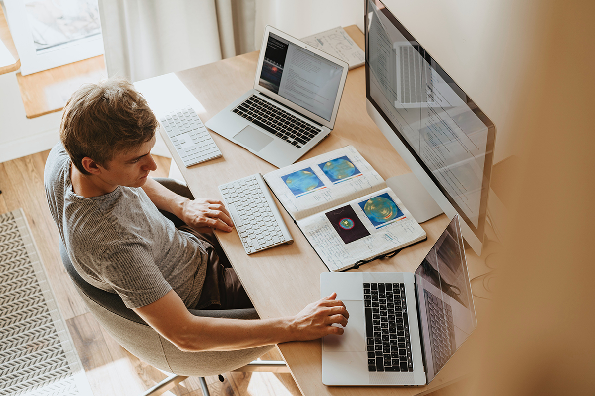 man in front of large computer monitor and 2 laptops
